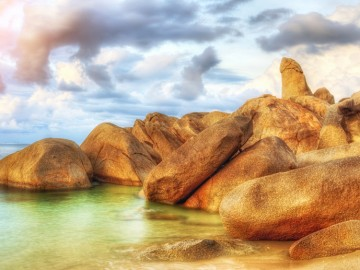 The Rock from Thai island of Koh Samui. The picturesque pile of rocks on the beach, illuminated by the sunrise