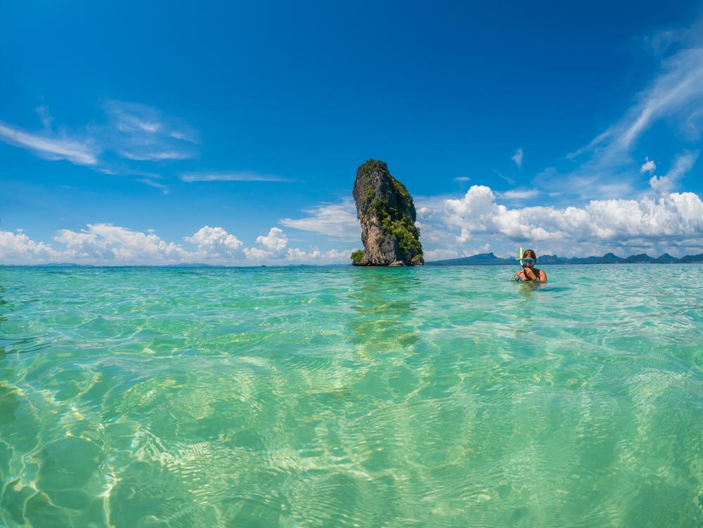 Beautiful woman snorkelling in Krabi Thailand taking underwater photographs