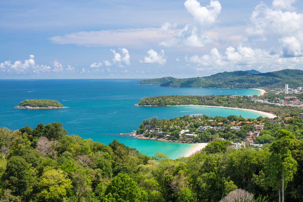 Beautiful turquoise ocean waves with boats and coastline from high view point. Kata and Karon beaches Phuket Thailand